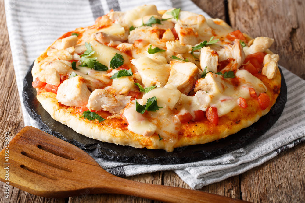 Delicious food: buffalo pizza with chicken breast, tomato concasse and mozzarella cheese close-up on the table. horizontal