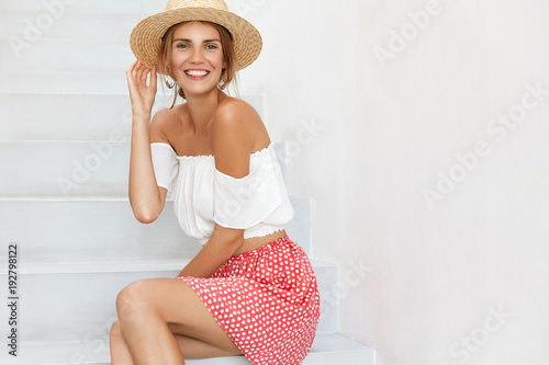 Fotografie, Obraz  Portrait of cheerful female in stylish top, polka dot skirt and straw hat poses at white stairs, going to have walk at beach, expresses positiveness