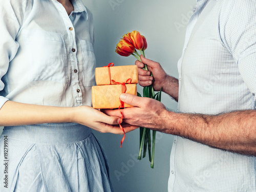 handsome man giving a gift and flowers to his beloved woman buy