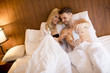 Loving young couple in the bed with mobile phone