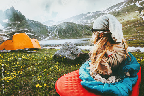 Fotobehang Kamperen Camping travel vacations woman relaxing in sleeping bag on mat enjoying mountains landscape Lifestyle concept adventure weekend outdoor harmony with nature