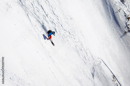 Fotomural Female freerider skiing down steep slope