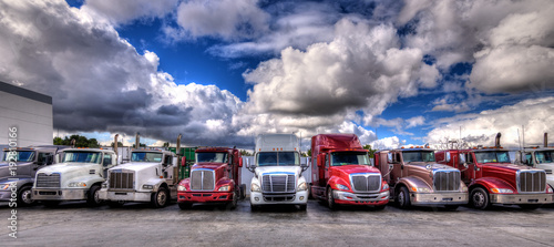 Obraz na plátne HDR image of Semi trucks lined up on a parking lot