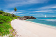 Sandy beach with palm and a white sailing yacht in the turquoise sea on La Digue island, Seychelles.