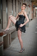 Sensual girl with long legs, short black dress and high heels posing provocatively .Handsome girl wearing short skirt and high heels in urban scene.Fashion model with long sexy legs on the street