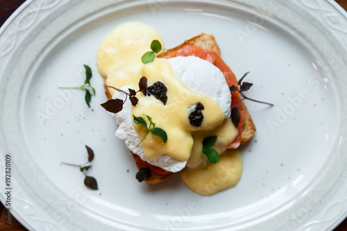 A horizontal image of eggs benedict on a white plate Wallpaper Mural