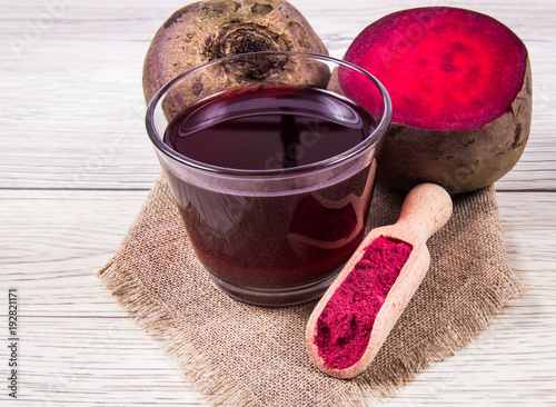 Healthy beetroot juice and fresh vegetables on wooden background.