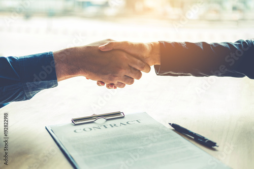 Fototapeta Business people negotiating a contract handshake between two colleagues obraz