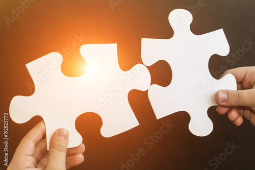 child s hands holding two big puzzle pieces baby connecting jigsaw