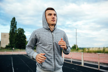Close-up Portrait Of A Handsome Running Sportsman, Wearing Sweatshirt With Hood And Listening To Music, At The Stadium