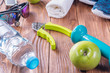 Set for sports activities on brown wooden background. Healthy lifestyle concept. Sport equipment, sport shoes, measuring tape, dumbbell, hand expander, towel, apples and bottle of water