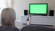 Woman Using Television Remote In Green Screen. Young Woman watching television with green screen, shot behind models shoulders