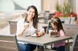 Beautiful Hispanic brunette with daughter at cafe