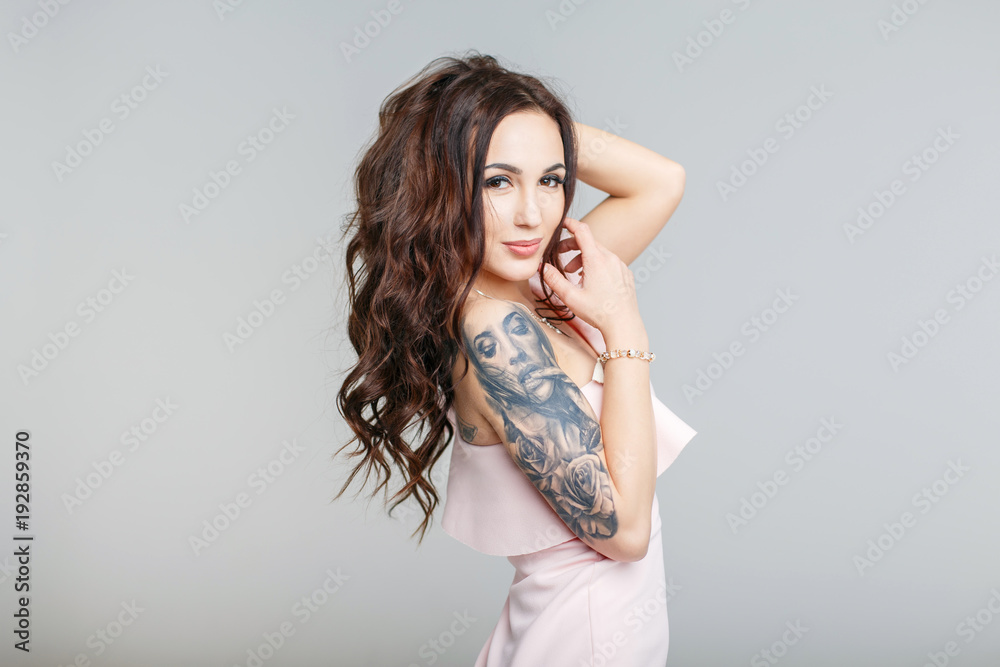 Fototapeta Beautiful young woman with stylish tattoo on hand in pink dress on gray background