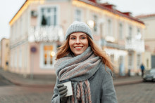 Magical Happy Portrait Of A Young Woman With A Smile In A Fashion Vintage Coat And A Gray Knitted Cap With A Fashionable Scarf With Coffee Walks In The City