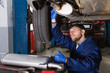 Young man is repairing car on her workplace
