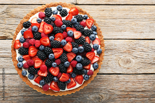 Fotomural Sweet tart with berries on grey wooden table