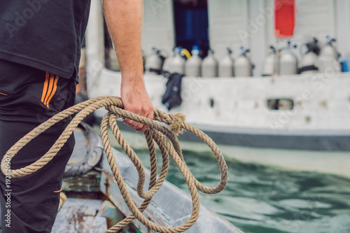 Photo A man throws a rope to moor on a diver ship