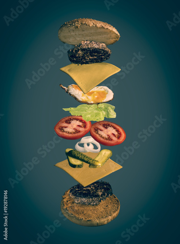 image shows an exploded view of a burger decorated with toppings like fried egg, lettuce, cheese, patty, onions