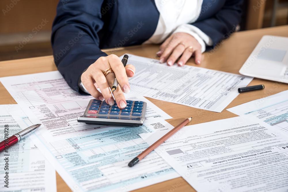 Fototapeta Woman filling US 1040 tax form 2018 year