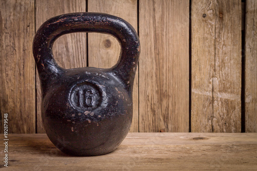 Old kettlebell on wooden deck