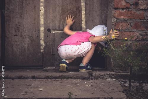 Fotografía Curious child lookinginto dark hole in barn door in countryside shed concept cur