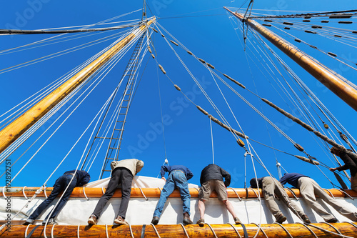Poster Zeilen Crew leans over the side of a big sailboat to raise the heavy sail on a tall ship at sea. Takes six strong people to hoist the canvas sail. Theme for teamwork, cooperation
