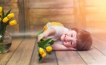 A Small Child With A Bouquet Of Yellow Tulips. A Boy With A Gift
