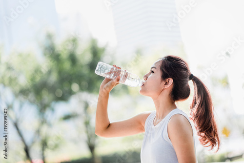 Shot of a young Asian woman drinking water from water bottle after jogging in the park.