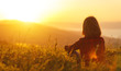 canvas print picture - Woman sits with her back in the field and look sunset in the mountains