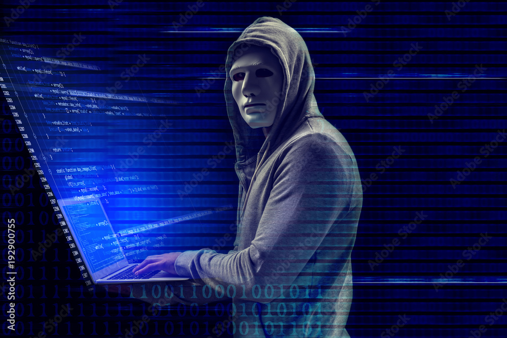 Fototapeta Hacker in mask with laptop on dark background