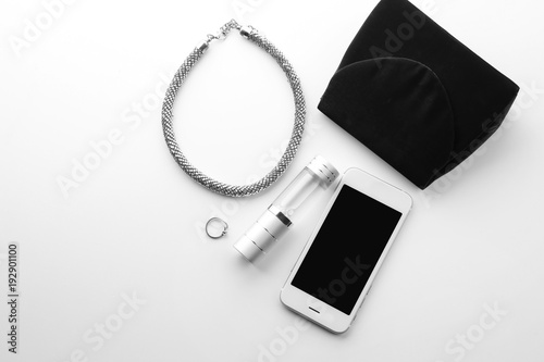 Bottle of perfume, smartphone and necklace on white background Canvas Print