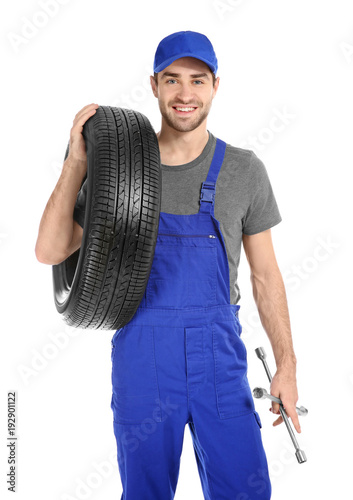 Tela Young mechanic in uniform with car tire on white background