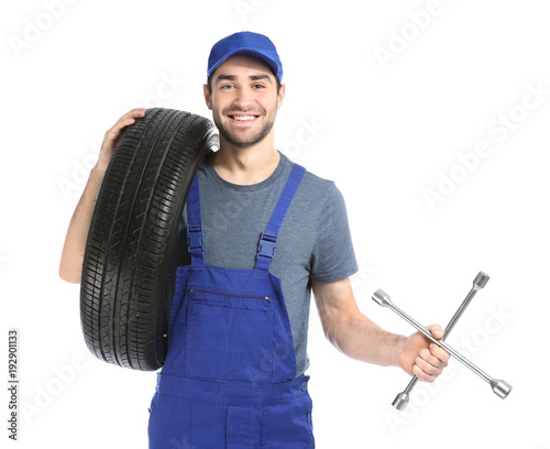 Fototapeta Young mechanic in uniform with car tires on white background obraz