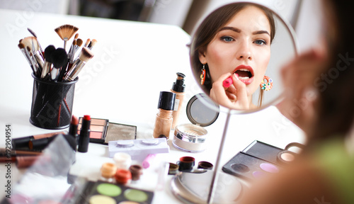 Fotografie, Obraz  Young beautiful woman making make-up near mirror,sitting at the desk