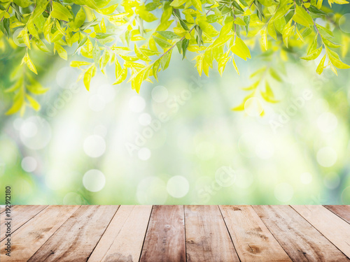 Fototapeta Wooden table top over green leaves abstract background obraz na płótnie