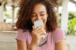 Joyful pretty African American female laughs at funny joke, surfes internet on mobile phone, reads good news, spends free time at cafe, connected to wireless internet. Technology and leisure concept