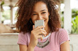 Glad African American female laughs at funny anecdote read in internet on mobile phone, demonstrates positiveness and happiness. Joyful dark skinned pretty woman spends free time at restaurant