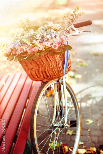 Deurstickers Fiets Bike with basket of spring flowers in park near bench in sunlight in sunset or sunrise. Beginning of new season of discounts.