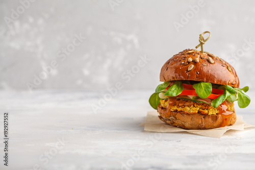 Vegan lentils burger with vegetables and curry sauce. Light background, copy space. Healthy vegan food concept.