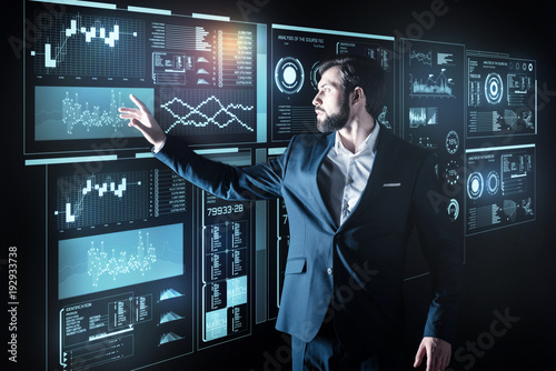 Fototapety, obrazy: Calmness. Attentive thoughtful young programmer standing near the powerful futuristic device and touching its transparent screen while being at work