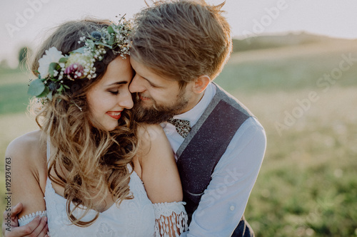 Obraz Beautiful bride and groom at sunset in green nature. - fototapety do salonu