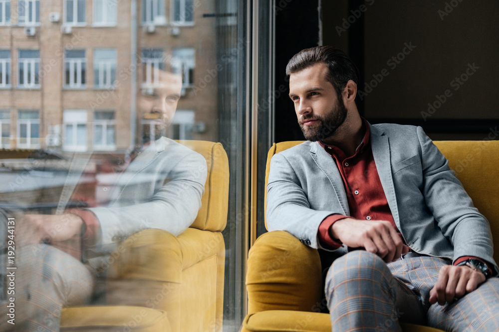 Fototapeta Handsome bearded man sitting on yellow couch at window with reflection