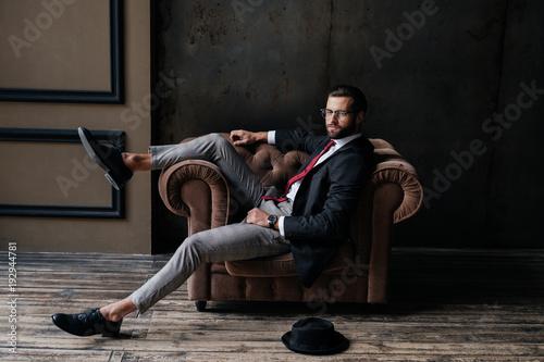 Vászonkép handsome elegant businessman posing in armchair, hat lying on floor near, loft i