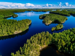 Fototapeta Rzeki i Jeziora Aerial view of blue lakes and green forests on a sunny summer day in Finland.