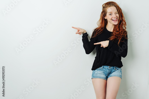 Laughing young woman pointing to copy space
