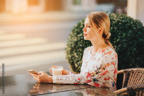 Outdoor portrait of beautiful woman resting in cafe with cup of coffee Poster