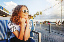 Young Beautiful Woman Girl In A Striped T-shirt Sitting In A Street Cafe Smiling, Seaside Town, Vacation And Travel