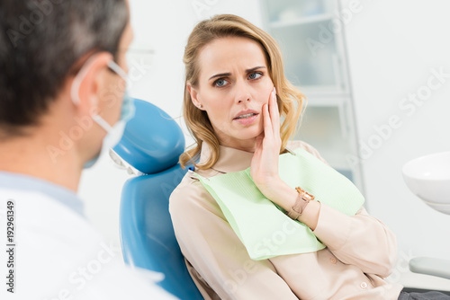 Carta da parati Female patient concerned about toothache in modern dental clinic