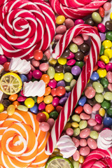FototapetaBackground of colorful chocolate candies, lollipops, candy cane and marshmallows